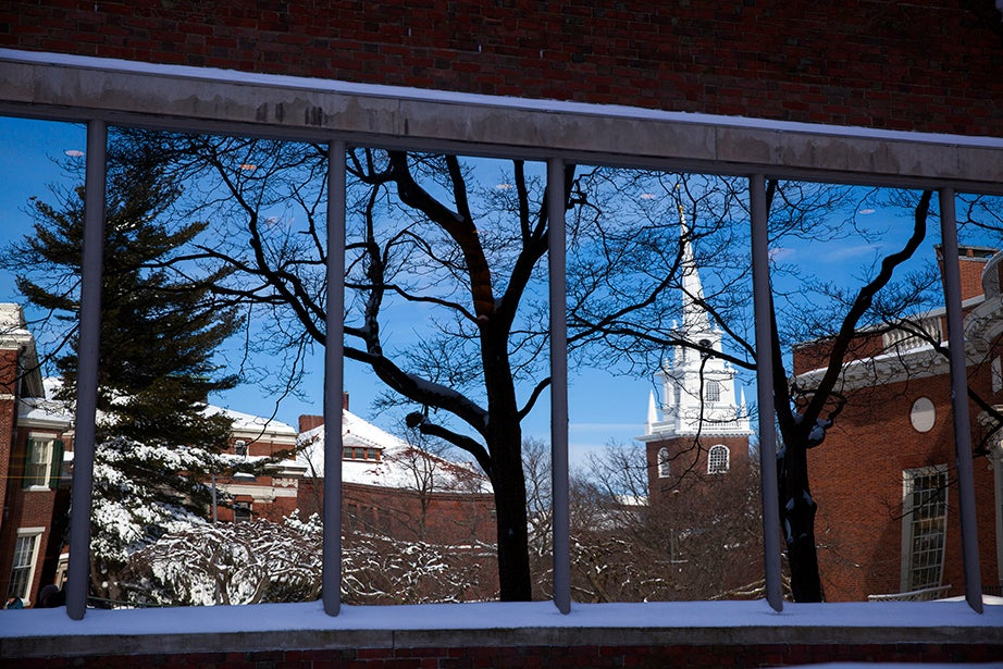 Loeb House, the tower of Memorial Church, and Houghton Library are reflected in the window of Lamont Library. Stephanie Mitchell/Harvard Staff Photographer