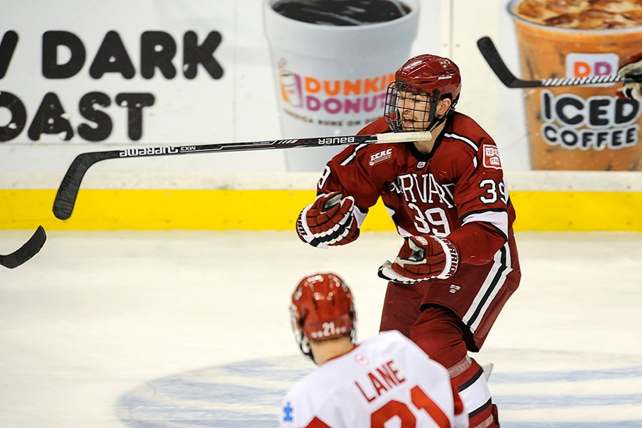 Crimson forward Brian Hart '16 reaches for his airborne stick after colliding with a BU player. Jon Chase/Harvard Staff Photographer
