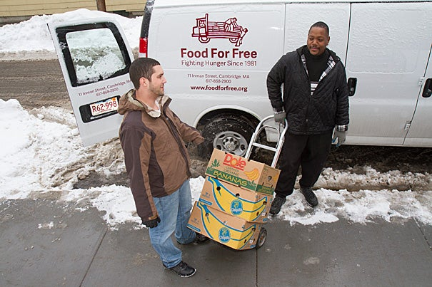 Director of programs at the Cambridge Community Center Darrin Korte (left) and Adam Collins wheel cartons of food from the Food for Free van into the center, which is one of the local organizations receiving donations from Harvard.