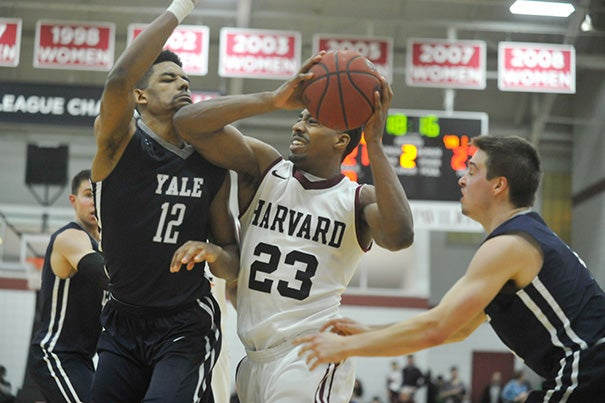 Crimson guard Wesley Saunders is hemmed in beneath the basket by two Yale defenders. Yale won, 62-52, and clinched at least a share of the Ivy title.