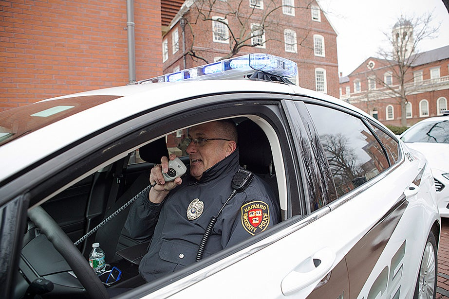 The Harvard University Police Department used the Green Revolving Fund to convert its entire fleet of patrol cars to hybrids, in a move to save money and help reduce greenhouse gas emissions and pollution. Anthony Carvello talks on the radio in the new car. Photo by Katherine Taylor