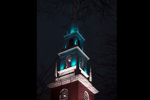 Harvard University's Memorial Church steeple is lit with teal lights in recognition of Sexual Assault Awareness Month on campus.