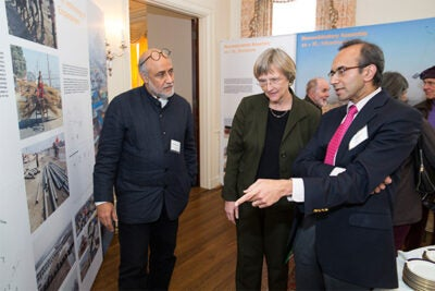 "The Harvard Kumbh Mela team gathered at Loeb House to reflect on the experience and to launch a book and exhibit on their findings, ""Kumbh Mela: Mapping the Ephemeral Megacity."" Professor of Urban Design and Planning Rahul Mehrotra (from left), President Drew Faust, and Tarun Khanna, director of the South Asia Institute, discussed the exhibit. Khanna, born in India, set aside his professorial mien when he took his parents to the festival and took a ritual bath in the river water."
