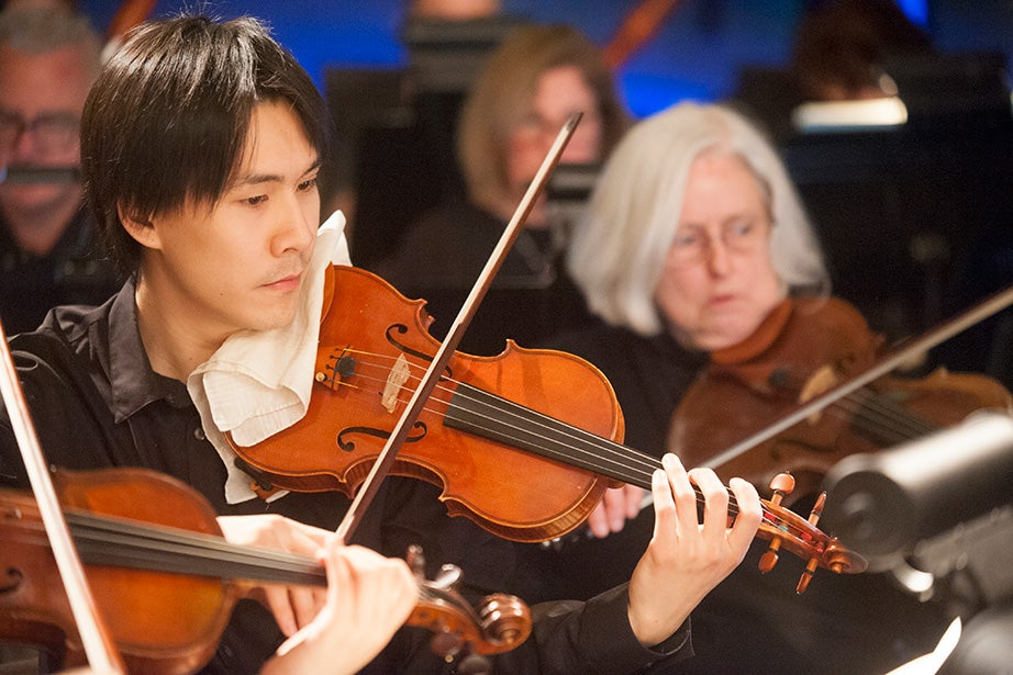 Aaron Kuan (left), a graduate student in the School of Engineering and Applied Sciences, and Mary Hecht, a library e-resources support specialist, play with the orchestra
