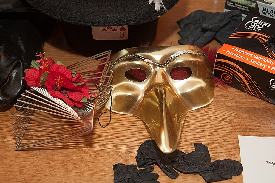 Theater accessories including a golden mask are left on a table after performers have left the dressing room.