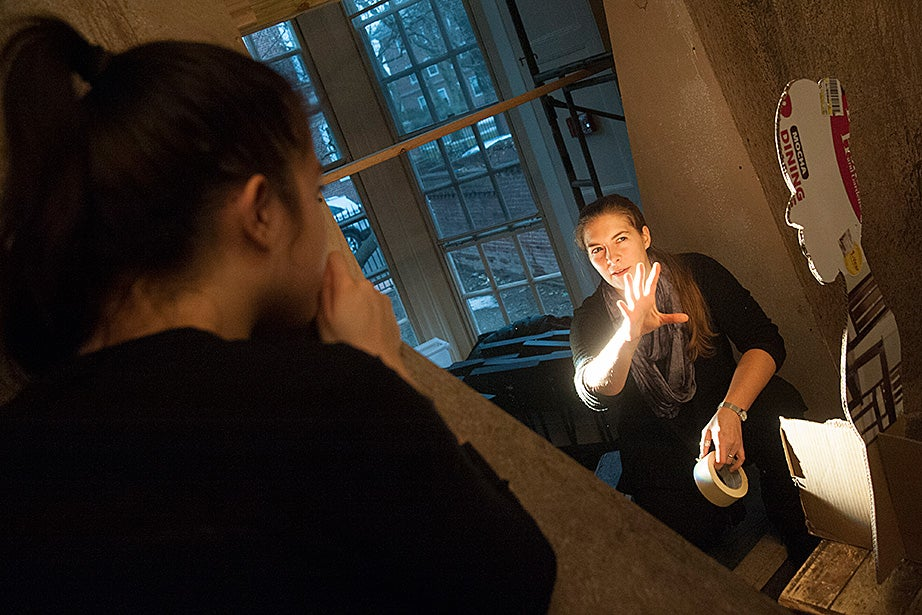 Stage manager Diana Smith '17 (left) and director Roxanna Myhrum '05 adjust a shadow puppet to cast an image on stage.