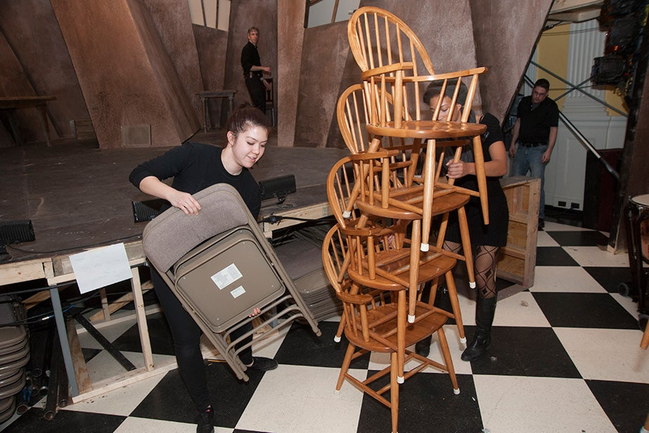 Stage manager Diana Smith '17 (left) sets up folding chairs for the orchestra as Asia Stewart '18 (partially obscured) stacks dining-room chairs for removal before the performance.
