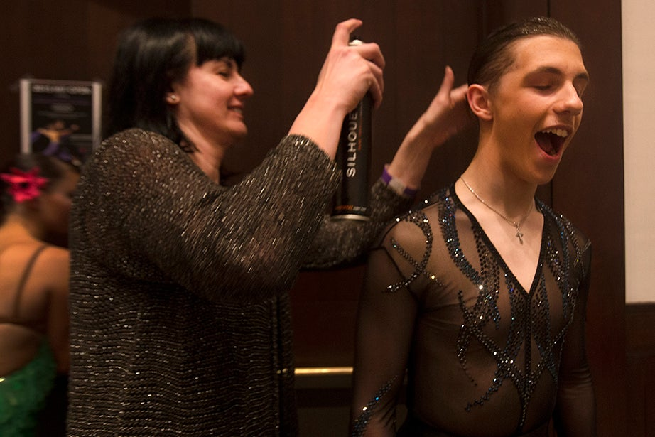 Irina Kogan helps Daniel Popovsky spray his hair into place during a break in the competition.