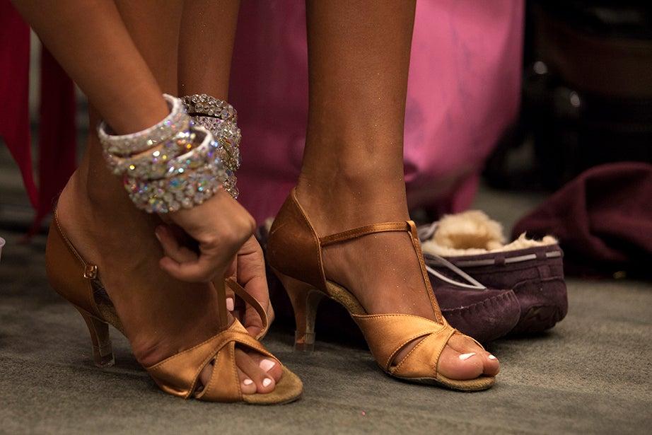 A dancer straps on her heels.