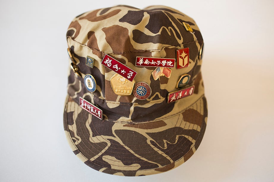 A camouflage ball cap with 15 pins, worn by American mathematician Alice Turner Schafer when she climbed the Great Wall of China in the 1990s. (Schlesinger Library)