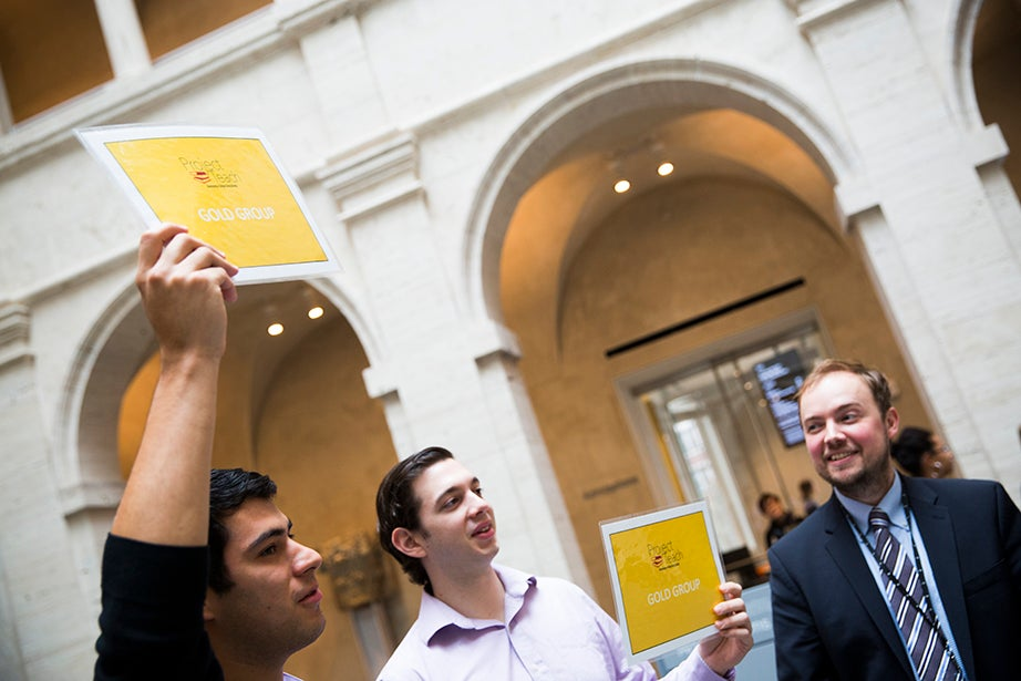 Inside the Harvard Art Museums' Calderwood Courtyard, Jesus Moran '16 (from left), Dominic Ferrante '15, and Rabb Curatorial Fellow Chris Molinski welcome scholars from Brooklyn's Mott Hall Bridges Academy. Stephanie Mitchell/Harvard Staff Photographer