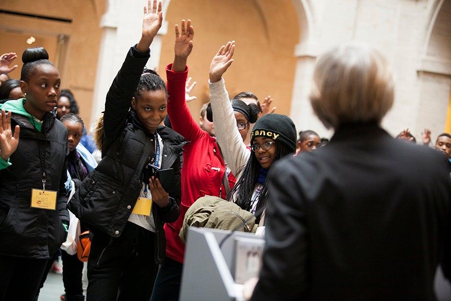 Harvard President Drew Faust welcomes the Mott Hall Bridges Academy students. Scholars raise their hands. Stephanie Mitchell/Harvard Staff Photographer
