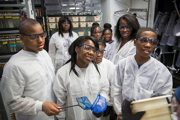 Students from Mott Hall Bridges Academy, Jermont Haines, Tukoya Boone, and Aaron Abdulmalik, learn how zebrafish are used in scientific research to study embryonic development with Tessa Montague, GSAS student inside the Biology Labs at Harvard University. In the background is Zion Edwards, (left) Tukoya Boone, Halle Bohner, and Bianca Nfonoyim '15. Harvard University Staff Photo: Kris Snibbe