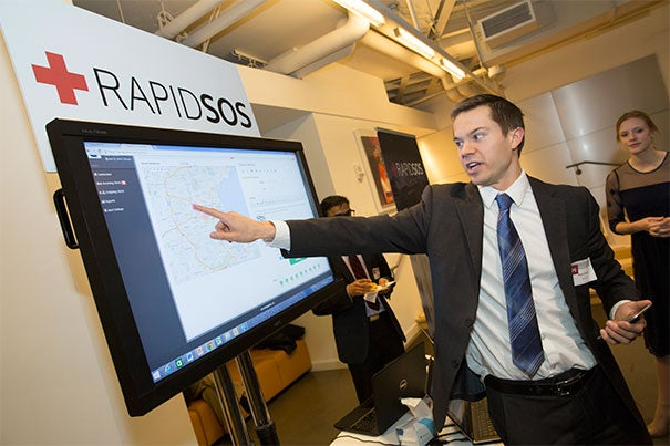 Harvard Business School student Michael Martin (photo 1) explains the grand prize winner RapidSOS to onlookers. President Drew Faust and i-lab Managing Director Gordon Jones discuss a project called Porter's Referral Center with Upasaha Khadka from Harvard Kennedy School (photo 2). Alok Tayi, a postdoctoral fellow in chemical biology, explains TetraScience, which develops an Internet-of-Things platform for drug discovery.