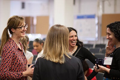 """Sarah Boyer (left) and Martine Zilversmit (right), co-founders of Harvard Graduate Women in Science and Engineering, speak with Harvard Professor Radhika Nagpal (center) during the """"WISE Beyond Your Years"""" symposium."""