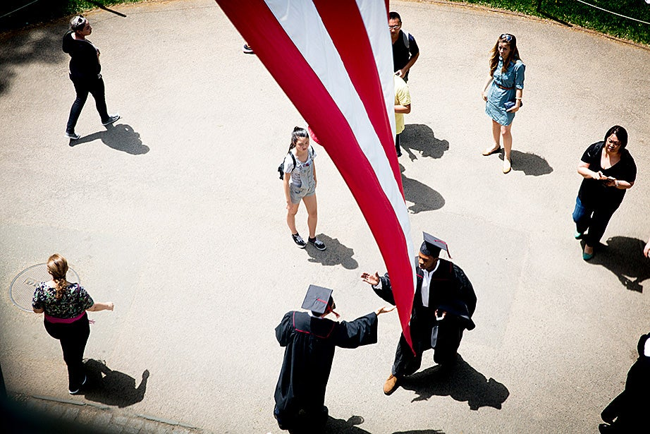 Students greet each other under the flag at University Hall prior to the Baccalaureate Service held each year inside the Memorial Church. Rose Lincoln/Harvard Staff Photographer