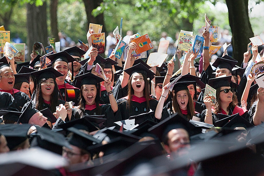 Graduates of the School of Education hold books overhead as they celebrate the conferral of their degrees. Jon Chase/Harvard Staff Photographer