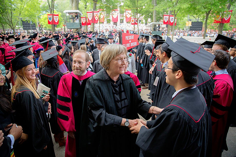 Harvard President Drew Faust greets Sietse Goffard '15 before Commencement. Provost Alan Garber is in the background. Kris Snibbe/Harvard Staff Photographer