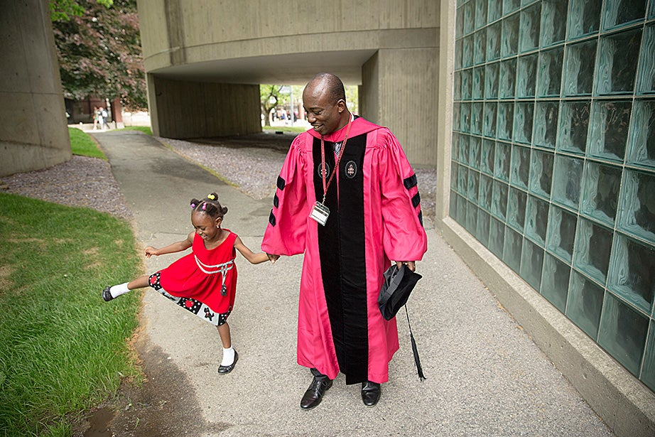 Raphael Arku, S.D. '15, and his 4-year-old daughter, Souzana, celebrate outside the Carpenter Center during Commencement. Kris Snibbe/Harvard Staff Photographer