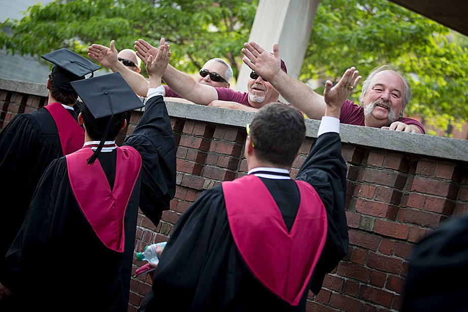 Custodians Bill Dyer (from right), Michael Shaw, Paul Hughes, and Tom Gallagher high-five graduates as they head into Tercentenary Theatre. Rose Lincoln/Harvard Staff Photographer