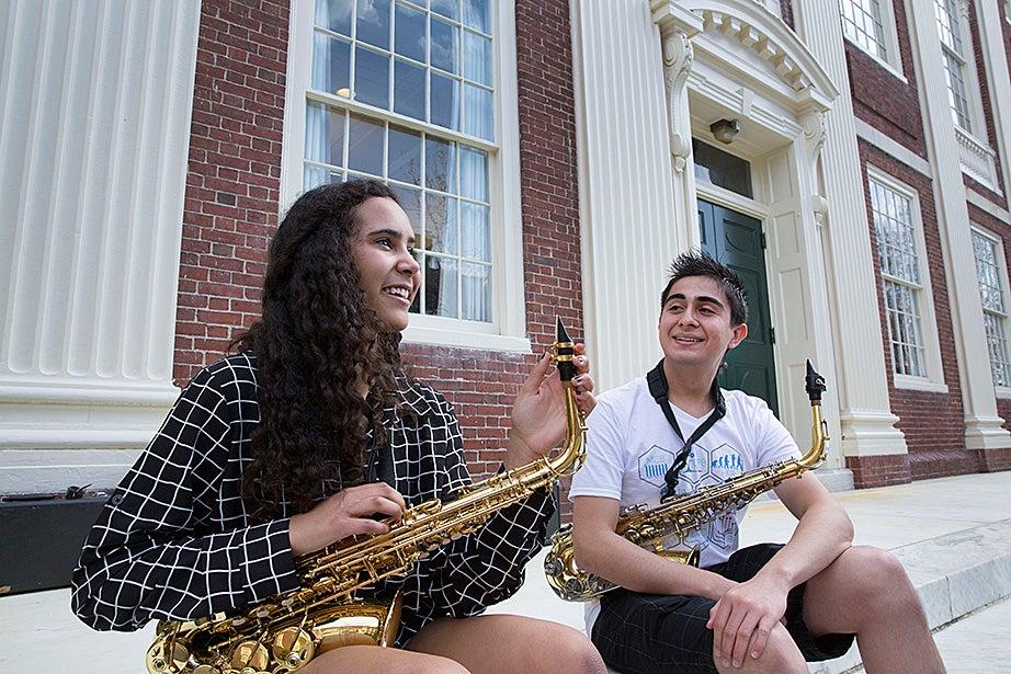 Mariah Goldsmith practices saxophone with volunteer David Armenta.