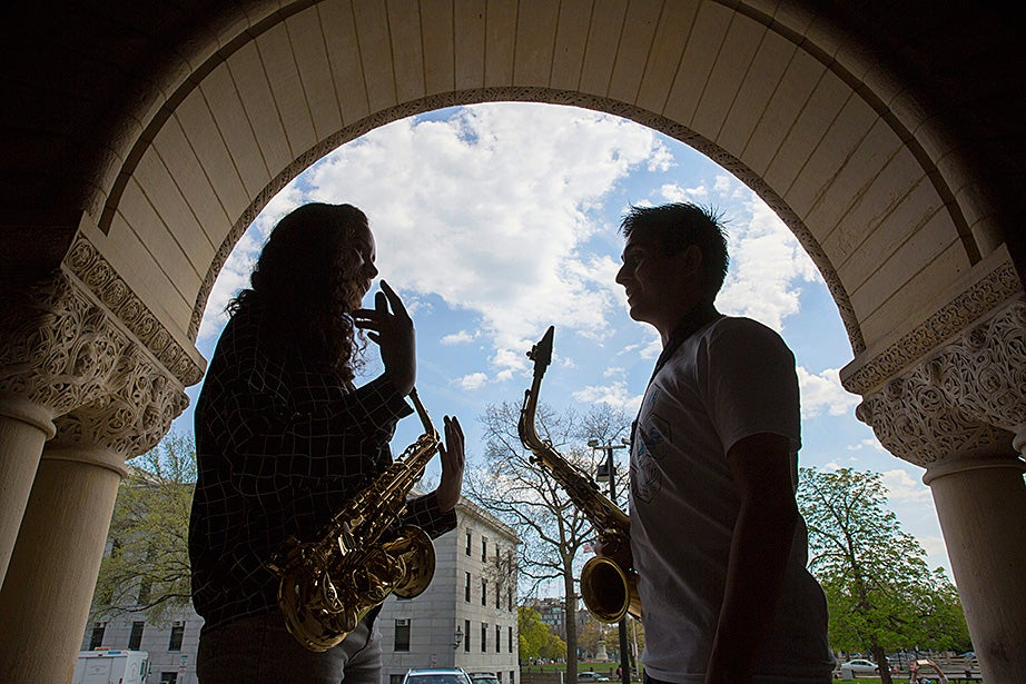 Framed by the arches of Austin Hall at the Harvard Law School, Mariah Goldsmith practices saxophone with volunteer David Armenta.