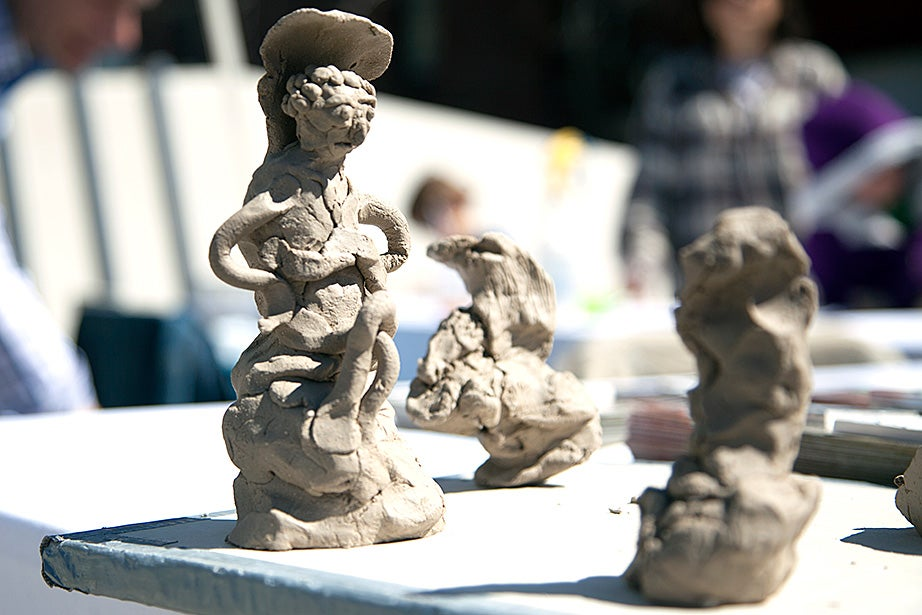Small sculptures sit on a table under a tent on the Science Center Plaza during Arts First. Photo by Kiera Blessing