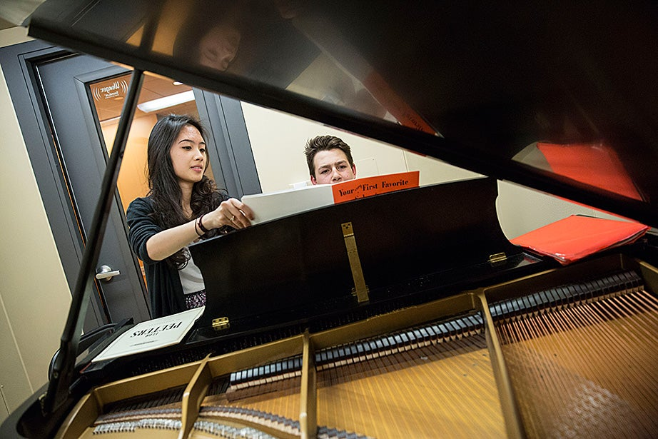 Volunteer Lucy Nam '17 works with Alex Sadock from the Cambridge Street Upper School inside a Paine Hall practice room.