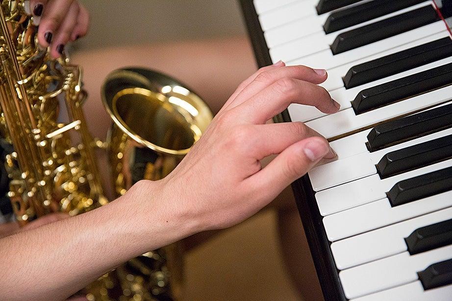 Mariah Goldsmith practices saxophone with David Armenta, who strikes a piano key.