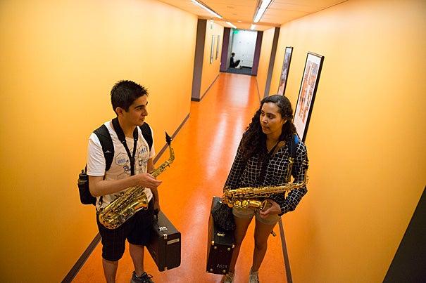 Mariah Goldsmith, a ninth-grader at Cambridge Rindge and Latin, walk through Paine Hall before a lesson with HARMONY volunteer David Armenta '17.