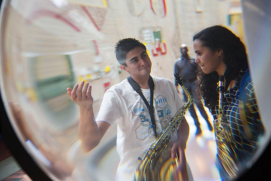 Ninth-grader Mariah Goldsmith is framed by a water lens in the Science Center while discussing an upcoming performance with her tutor, David Armenia.