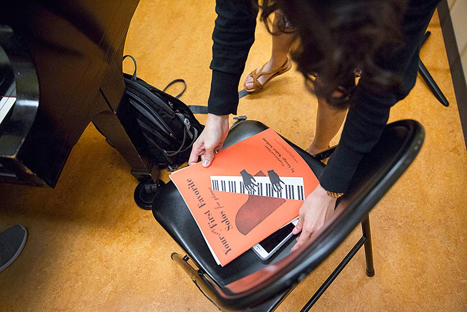 Lucy Nam unpacks music scores inside a Paine Hall practice room.