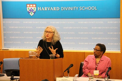 Buddhist ministers in the Western world are going out and working in hospitals and prisons with people who are not exclusively Buddhist. That can lead to a generalization or abstraction of certain types of practices such as mindfulness and compassion, said Harvard Professor Janet Gyatso (at podium). Cheryl Giles (right), lecturer on pastoral care and counseling, later talked about her transition from being a Roman Catholic to a practitioner of Buddhism.