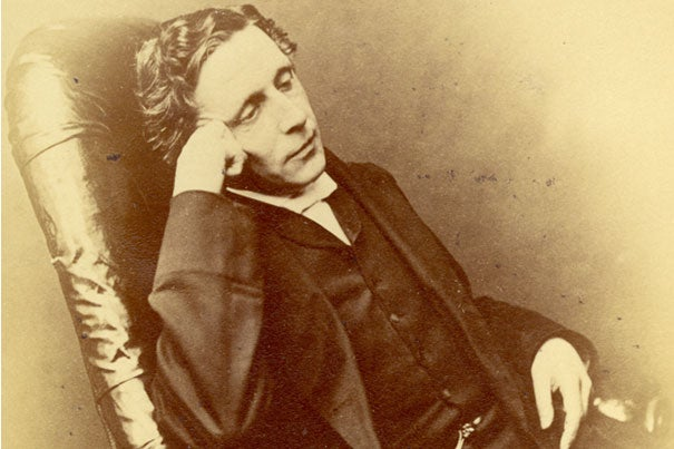 """Lewis Carroll (photo 1), author of """"Alice's Adventures in Wonderland,"""" used his own funds for the book's first printing but recalled the original copies due to their poor quality. One rare remaining original copy  was bound in white vellum (photo 2) and presented to Alice Liddell in 1865. Laura Larkin (left, photo 3) and Julia Featheringill prepare to photograph the materials, which will be on display at Houghton Library starting May 20."""