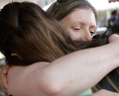 Katherine Kulik '15 gets a hug from her mother. Ned Brown/Harvard Staff