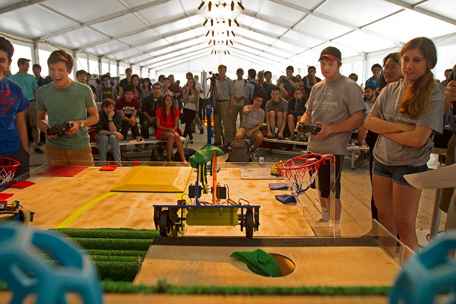 A crowd gathers to watch a competition between robots designed by Harvard students.