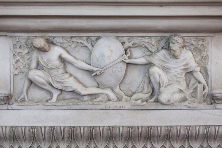 A stylized Veritas shield on a decorative marble molding in the dining room mantelpiece of Loeb House.