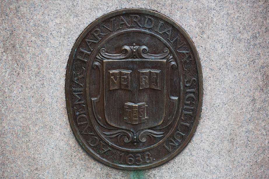 A Veritas shield on the John Harvard Statue follows the original 1643 design for the three books: two open and one turned over.