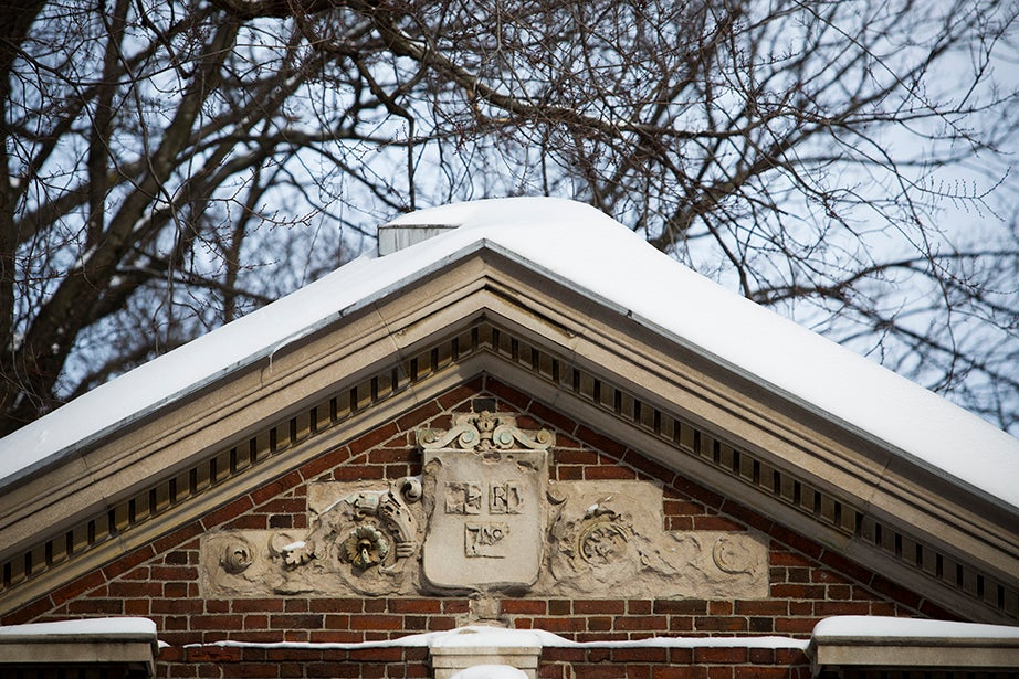 A heavily weathered Veritas shield above the McKean (Porcellian Club) Gate to Harvard Yard.