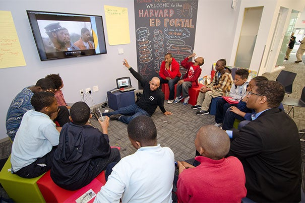 Boston Public Schools teacher Mwalimu Donkor Issa works with young men at the Harvard Ed Portal during the 2015 Dynamic Young Men's Leadership commencement celebration. The initiative  focuses on empowering young black and Latino men, encouraging them to pursue their dreams, and working closely with teachers and parents to provide students with tools for academic and professional success.