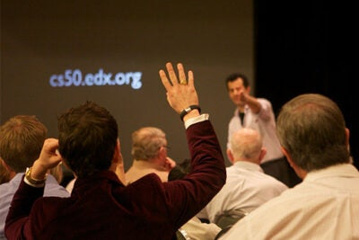 David Malan (facing audience), the Gordon McKay Professor of the Practice of Computer Science, discusses his introductory computer science course, CS50, with alumni in Texas.