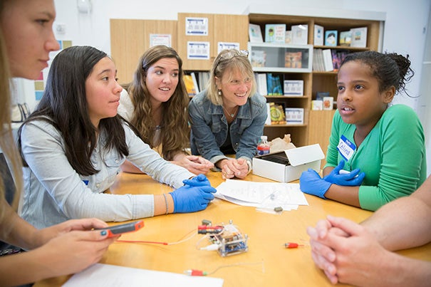 Katie Schmalkuche '16 (from left),  eighth-grader Jade Diaz of Brighton; Emily Henson, program manager for HarvardX at Allston; Susan Johnson, Ed Portal manager of teaching and curriculum; and Braintree East Middle School sixth-grader Cynthia Henderson learn the basics of neuroscience at the Ed Portal in Allston.