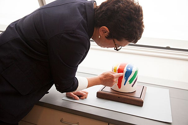 "Susan Dackerman (photo 1), consultative curator of prints, examines the design for the Boston Gas Co. tank created by Corita Kent in 1971. At the Harvard Art Museums, ""Corita Kent and the Language of Pop"" examines the artist's work within the context of the pop art movement and the social and cultural currents of the time. Inspired by a Del Monte food slogan and the reforms in the Catholic Church introduced during Vatican II, Kent's work ""the juiciest tomato of all"" (photo 2) evokes the everyday and the divine. Kent's painted gas tank (photo 3) became a ""pop art landmark for Boston,"" said Dackerman."