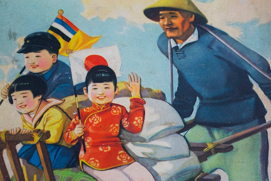 The government promoted an appearance of cross-cultural unity that stood at odds with the true social landscape. An illustration shows a laborer pushing happy children in Western and Chinese gear as they wave Japanese and Manchukuan flags.
