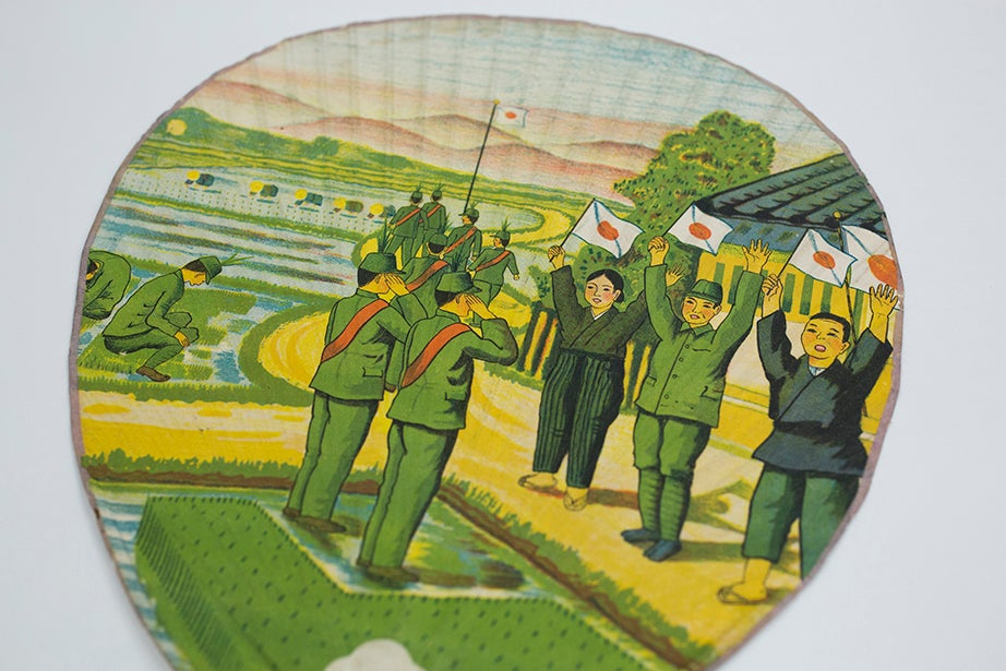 Japanese nationalism is evident on this fan featuring soldiers and workers with the Japanese flag.