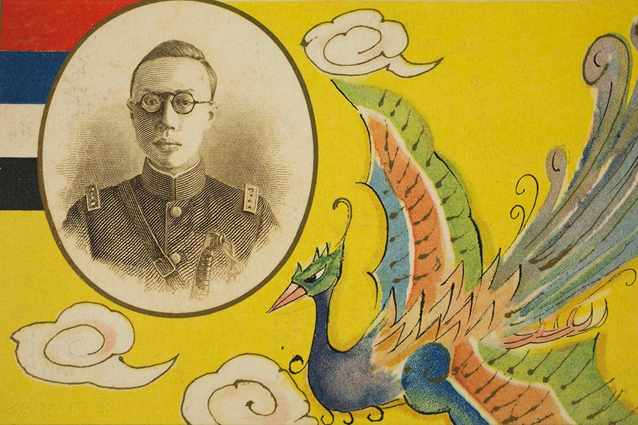 "A postcard features a portrait of the Qing ruler Puyi, essentially a puppet of the Japanese imperial government, on a background of the Manchukuo flag. The five colors on the flag represented ""five races under one union."""