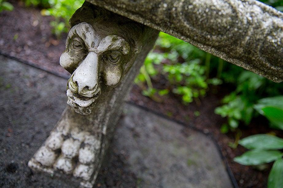 A gargoyle decorates the base of a bench.