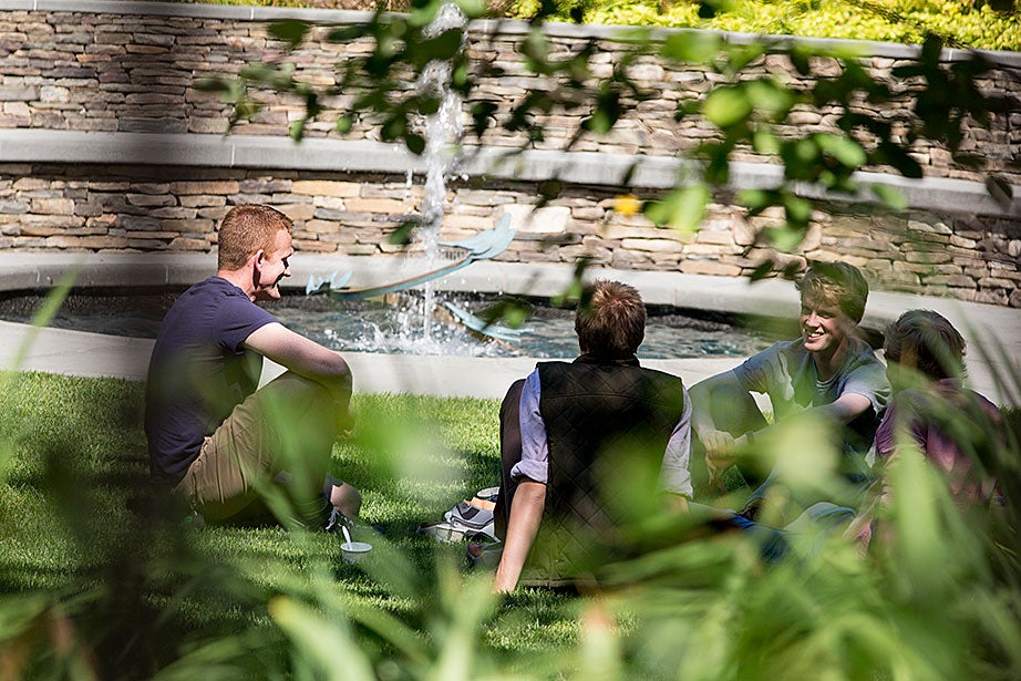 James Graham '17 (right) takes a break from class to converse with friends Matthew Bennett (left) and Alex and Marcus Rhodes at the Sunken Garden.