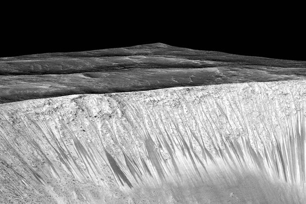 The dark streaks pictured are up to a few hundred yards, or meters, long. They are hypothesized to be formed by the flow of briny liquid water on Mars.