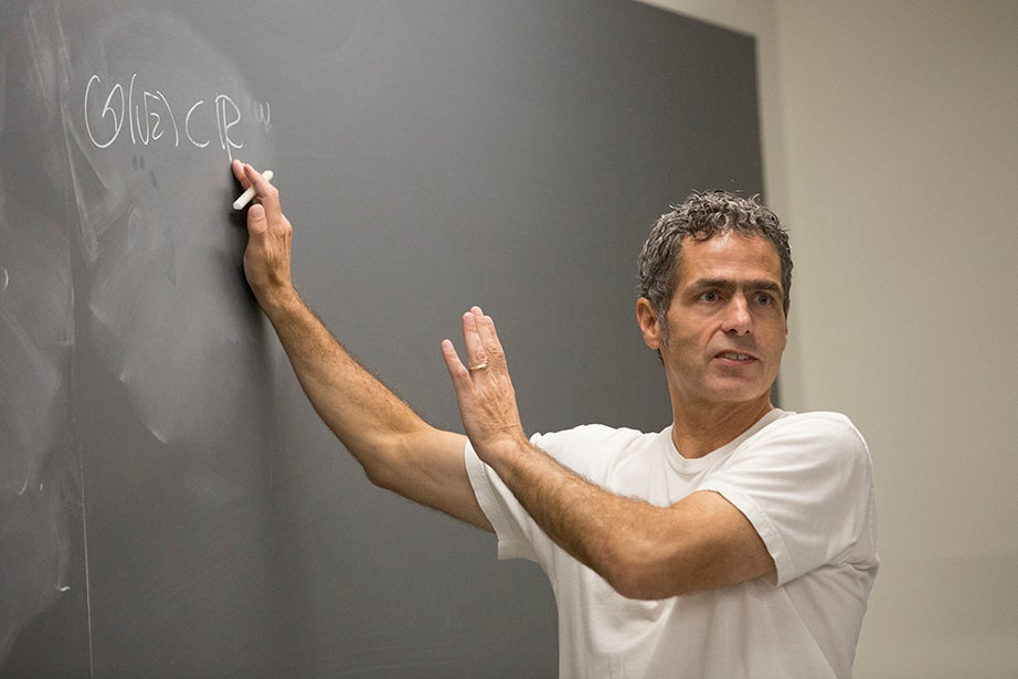 Michael Hopkins writes a math problem on a chalkboard. Jon Chase/Harvard Staff Photographer